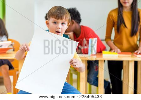 Kid Boy Holding Blank White Poster With Diversity Friends And Teacher At Background,kindergarten Sch