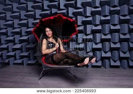Studio Photo Of Sexy Asian Woman In A Small Black Dress Sitting On A Chair With An Red-and-black Umb