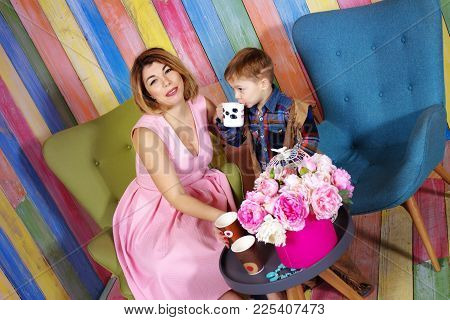 Cheerful Mother And Son Relaxing In Cafe Together. Studio Image