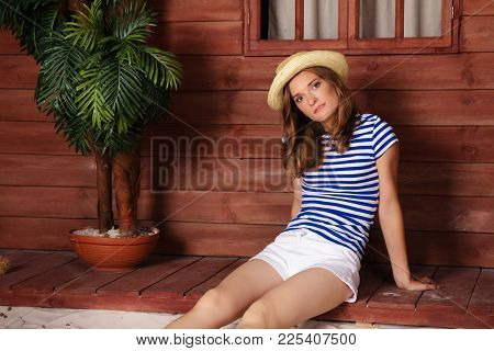 Beautiful Slim Woman In A White Shorts And Striped Shirt And A Hat Sitting On The Wooden Veranda Of