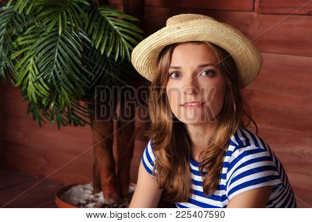 Blonde Lady With Straw Hat Sitting Near Wooden House And Looking At A Camera In Summer Time