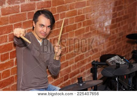 Handsome Drummer With Drum Sticks In His Hands Pointing On A Camera. Electronic Drums In A Musical C