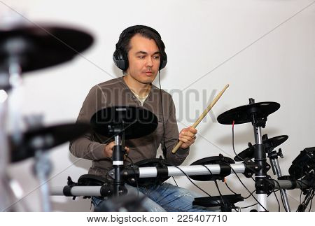 Drummer With Drum Sticks In His Hands Playing Electronic Drums In A Music Studio