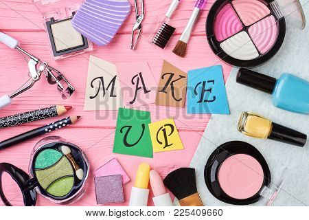 Fashion Make Up Products Background. Colorful Cosmetics Items On Pink Background. Multicolored Paper