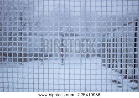 Snowed Sport Yard Behind Frosty Metal Net In Winter Time