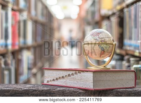 February 8, 2018 - Bangkok, Thailand: Globe Model On Textbook, Or Dictionary On  Table In School Or