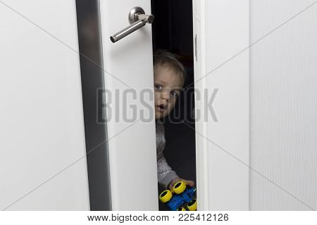Cute Toddler Looking Out From Behind The Ajar Door.