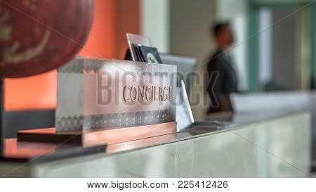 Concierge Service Desk Counter With Hotel Staff Team Working In Front Of Reception Hall For Tourist