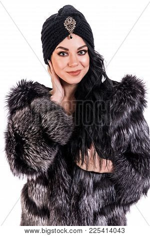 Pretty Young Woman In A Black Fur Coat And Turban Isolated Over White Background