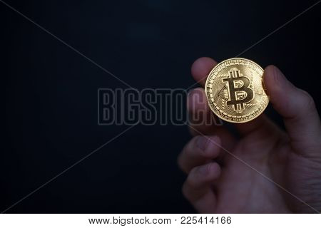 Hand Holding Cryptocurrency Golden Bitcoin Isolated On Dark Blue Background. Symbol Of Virtual Crypt