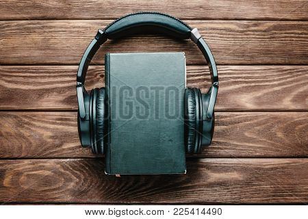 Headphones Around A Paper Book On A Wooden Background, Space For Text On The Cover Of Book. Concept