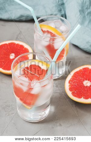 Cold Drink With Grapefruit And Ice On A Gray Concrete Background. Drink In A Glass With A Blue Tube