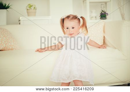 Cute two year old girl playing at home. Happy childhood.