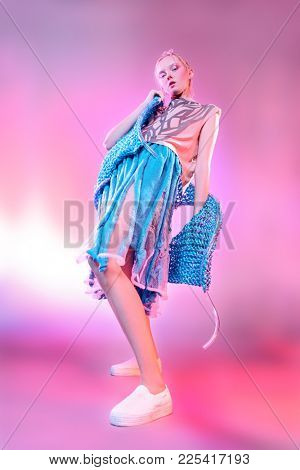 Vogue shot of a female model posing at studio. Fashion collection. Full length portrait over pink background.