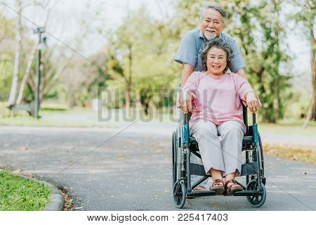 Happy Smile Asian Senior Woman In A Wheelchair Relaxing And Walking With Her Husband Outside At The