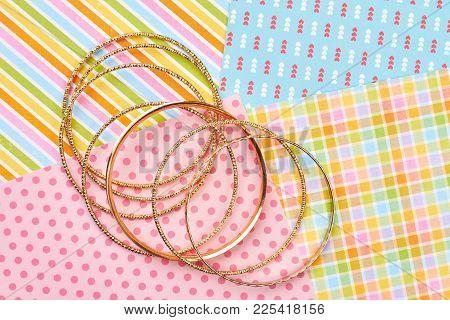 Set Of Golden Bracelets, Colorful Background. Female Bangles On Patterned Paper Background. Woman St