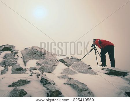 Photographer With Eye At Viewfinder Of Camera On Tripod Stay On Snowy Cliff And Takes Photos. Winter