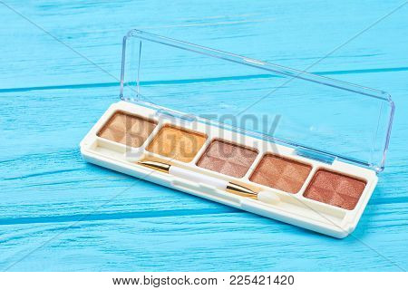 Brown Color Eyeshadows Palette. Set Of Nude Eyeshadows On Blue Wooden Background. Fashion Make Up Ac