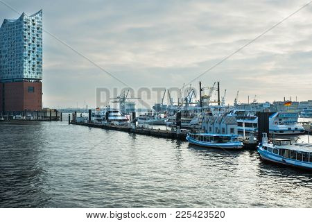 Hamburg, Germany - January 2018. The Harbor With Piers And Ships On The Quay And A View Of The Philh