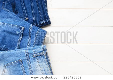 Top View Jeans On A Light Wooden Background. Detail Of Nice Blue Jeans. Jeans Texture Or Denim Backg
