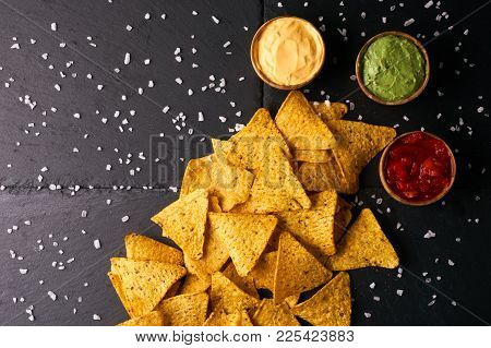 Mexican Nachos With Sauces Tomato Ketchup, Cheese And Guacamole In Wooden Bowl On Dark Background, T