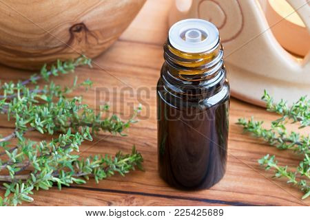 A Dark Bottle Of Thyme Essential Oil With Fresh Thyme Twigs In The Background