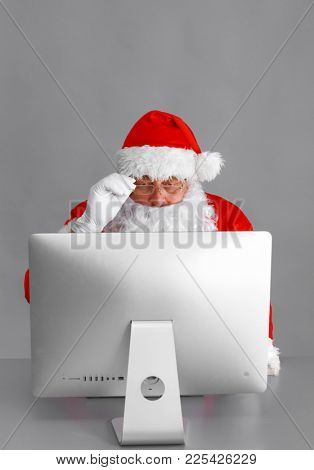 Santa Claus reading children letters and writing responses to them using laptop .