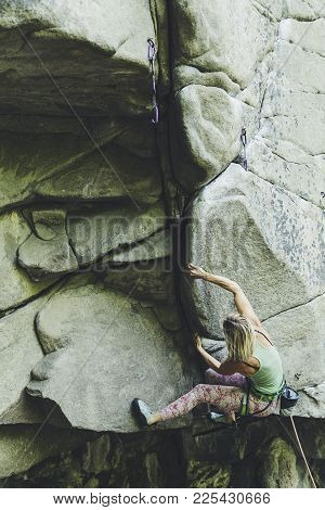 The Girl Climbs The Rock On A Climbing Route.