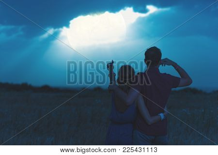 Couple Enjoying Under The Moonlight In Nature.