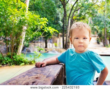 Child looking waterfall. Luang Prabang, Laos