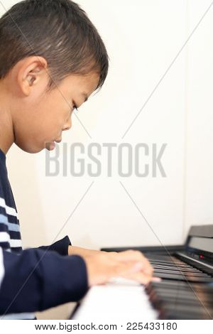 Japanese Boy Playing A Piano (second Grade At Elementary School)
