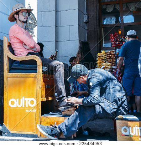 Shoe Shine Worker Shines A Client's Shoes In The Historic Centre Of Quito, Ecuador