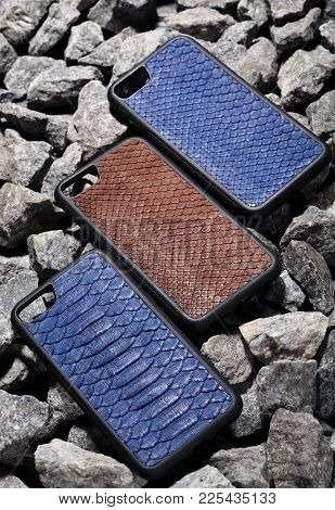 Three Exclusive Brown And Blue Snake Leather Case For Smartphone.luxury Case. On Stone Background
