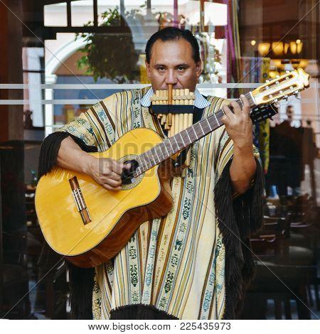 Quito, Ecuador, December 17, 2017: Local Ecuadorian Man Wearing Traditional Clothes Plays Guitar And