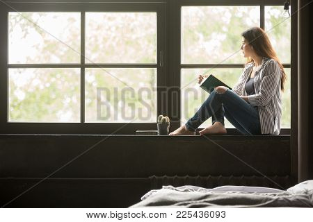 Pensive Dreamy Girl Holding Book Sitting On Sill At Home Looking At Big Window Dreaming, Thoughtful