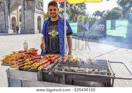Quito, Ecuador, December 17, 2017: Ecuadorian Street Seller Barbecuing Pork And Chicken On The Stree