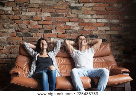 Young Happy Couple Relaxing On Comfortable Leather Couch At Home, Relaxed Smiling Man And Woman Rest