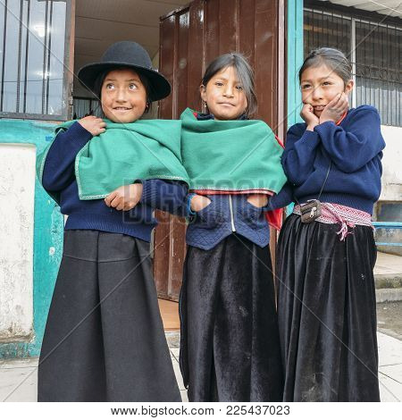 Tungurahua, Ecuador - Dec 20, 2017: Young Ecuadorian Indigenous Schoolgirls Pose For A Picture Outsi