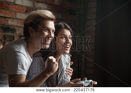 Young Girl Gamer Holding Joystick Controller Winning Video Game With Help Of Excited Boyfriend Teach