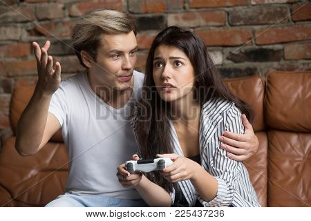 Angry Man Scolding Nervous Young Woman For Losing Videogame, Worried Girl Playing Video Game At Home
