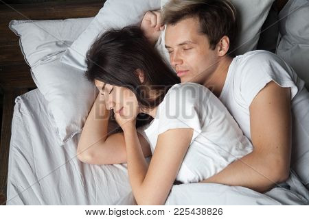 Young couple sleeping together embracing cuddling on comfortable bed, loving man hugging beautiful woman lying asleep on soft pillow, enjoying healthy peaceful sleep in bedroom, dozing in the morning poster