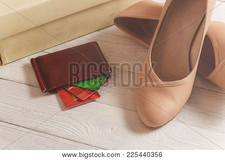 Box, Wallet, Credit Cards And Womans Shoes Lying On The White Wooden Background.