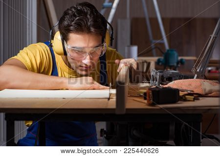Worker working in repair workshop in woodworking concept