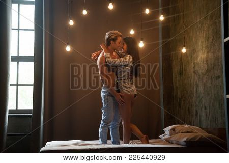 Romantic Young Sexy Couple Embracing Getting Closer To Kiss Standing On Bed Together With Vintage Li