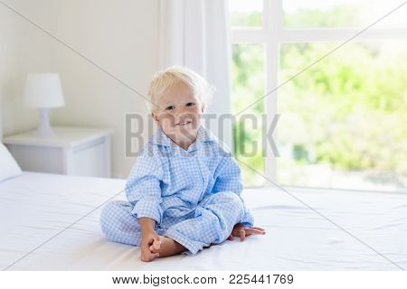 Kids Playing In Parents Bed. Children Wake Up In Sunny White Bedroom. Little Boy In Blue Pajamas. Sl
