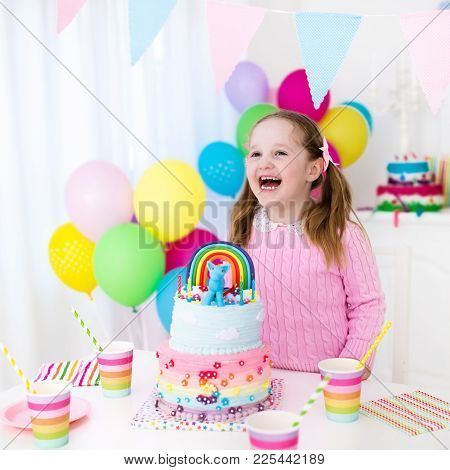 Kids Birthday Party. Child Blowing Out Candles On Colorful Cake. Decorated Home With Rainbow Flag Ba