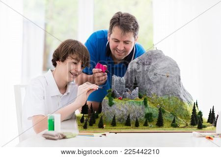 Father And Son Work On Model Building School Project. Kids And Parent Build Miniature Scale Model Mo