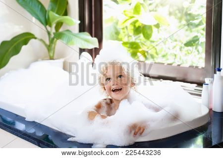 Little Child Taking Bubble Bath In Beautiful Bathroom With Big Garden View Window. Kids Hygiene. Sha