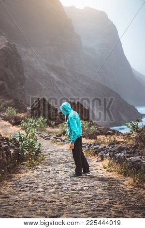 Tourist In Hoodie In Aranhas Valley Hiking To Ponto Do Sol. Huge Mountains Of Coastline And Old Loca