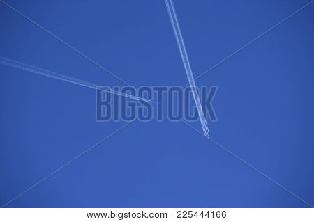 Two  Jet Aircraft With Exhaust Vapour Trails In Clear Blue Sky